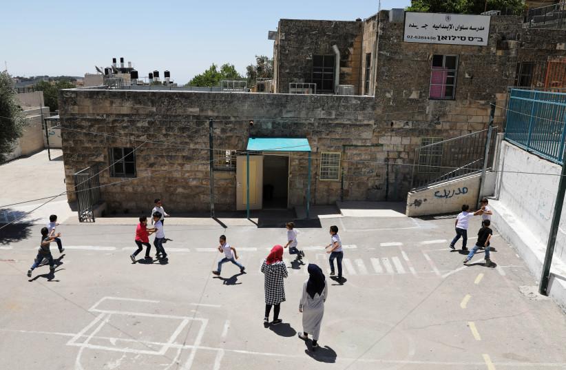 Palestinian children play on a court at a school in the East Jerusalem neighbourhood of Silwan June 19, 2017. Picture taken June 19, 2017. (photo credit: REUTERS/AMMAR AWAD)