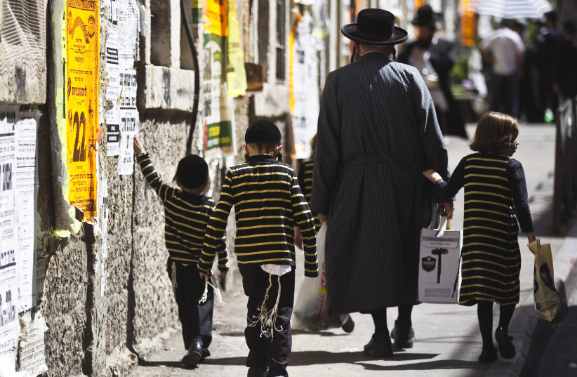 An ultra-Orthodox Jewish man walks with his children on a street in Jerusalem's Mea Shearim neighbourhood September 24, 2015. (photo credit: REUTERS)