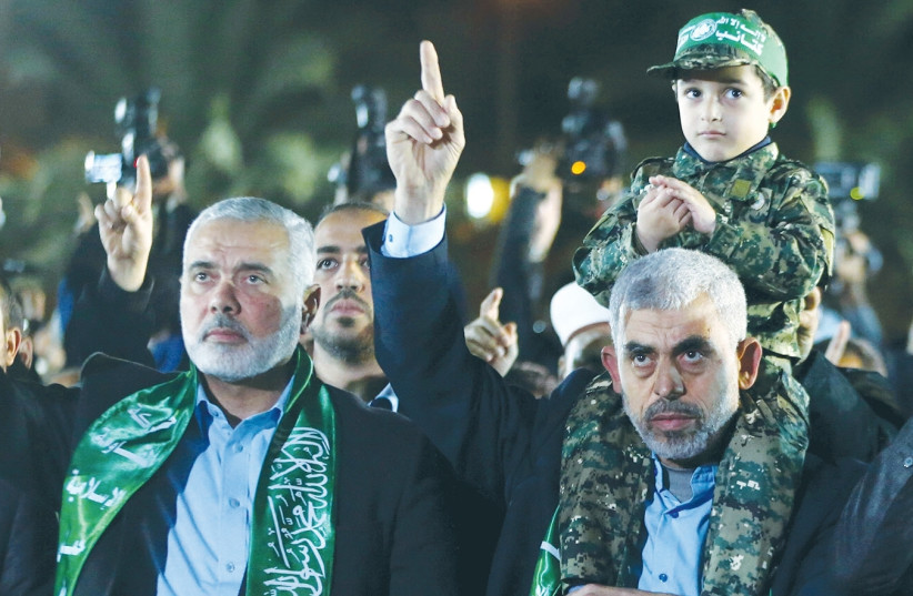 THE SON OF Hamas military leader Mazen Fuqaha sits on the shoulders of Hamas Gaza chief Yahya al-Sinwar as Hamas politburo chief Ismail Haniyeh gestures during a memorial service for Fuqaha in Gaza City in March. (photo credit: REUTERS)