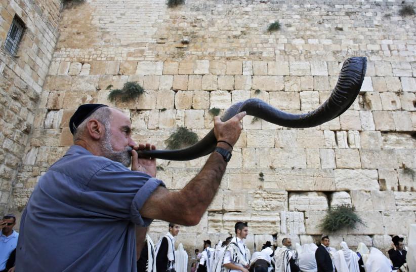 A Jewish worshipper blows a Shofar,  at the Western Wall ahead of Rosh Hashana (photo credit: AMMAR AWAD/REUTERS)