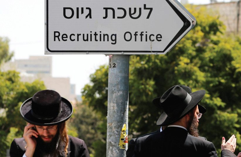 ULTRA-ORTHODOX MEN walk past the entrance to an IDF draft office in Jerusalem. (photo credit: REUTERS)