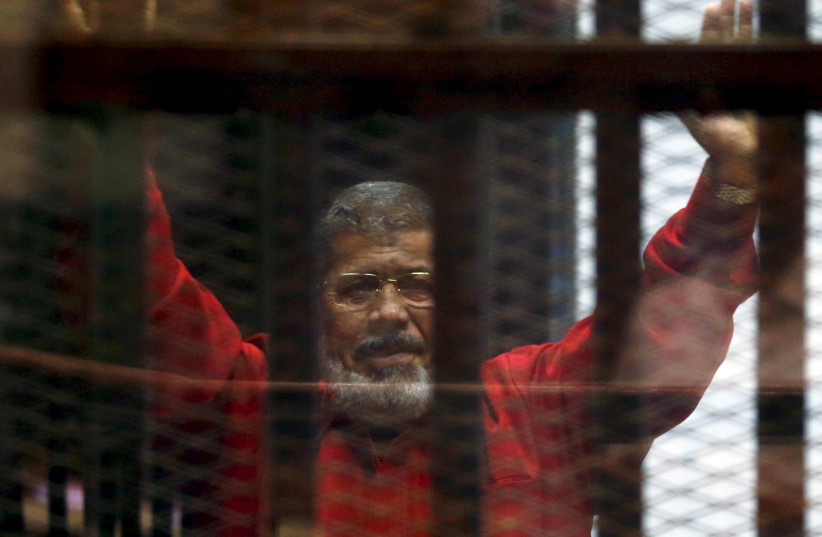 Ex-President Mohammad Morsi seen through prison bars in 2016  (photo credit: REUTERS/AMR ABDALLAH DALSH)