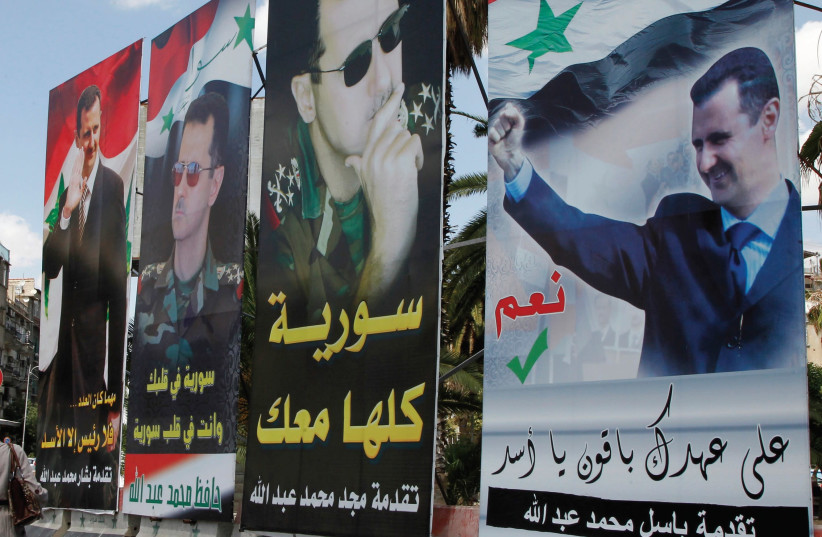 A woman walks past election posters of Syria's President Bashar Assad along a street in Damascus in 2014. (photo credit: REUTERS)