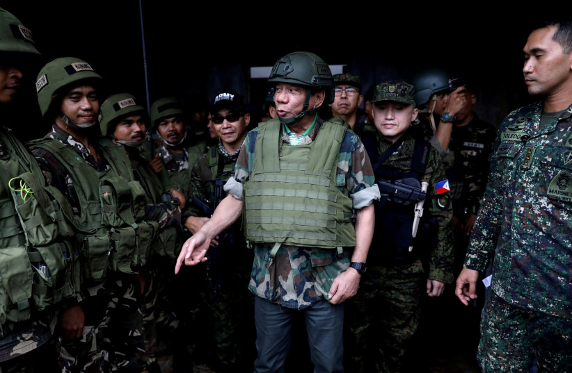 Philippine President Rodrigo Duterte wears a bulletproof vest and a helmet as he gives a pep talk to troops fighting the extremist Maute group in Marawi, Philippines August 24, 2017. (photo credit: REUTERS)