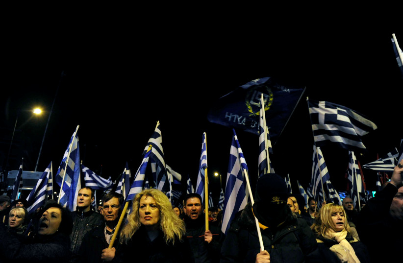 Supporters of Greece's far-right Golden Dawn party shout slogans as they wave national and party flags during an annual rally to commemorate the 21st anniversary of the Imia dispute, in Athens, Greece January 28, 2017.  (photo credit: MICHALIS KARAGIANNIS/ REUTERS)