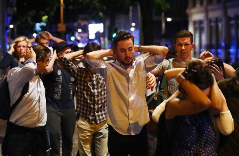 People leave the London Bridge area with their hands up after a terrorist attack (photo credit: NEIL HALL/REUTERS)