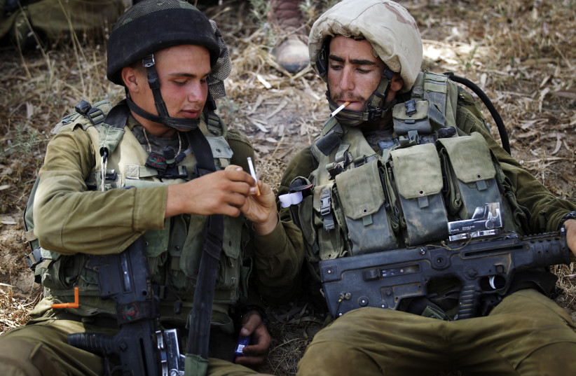 IDF soldiers share cigarettes while resting in the shade (photo credit: FINBARR O'REILLY / REUTERS)
