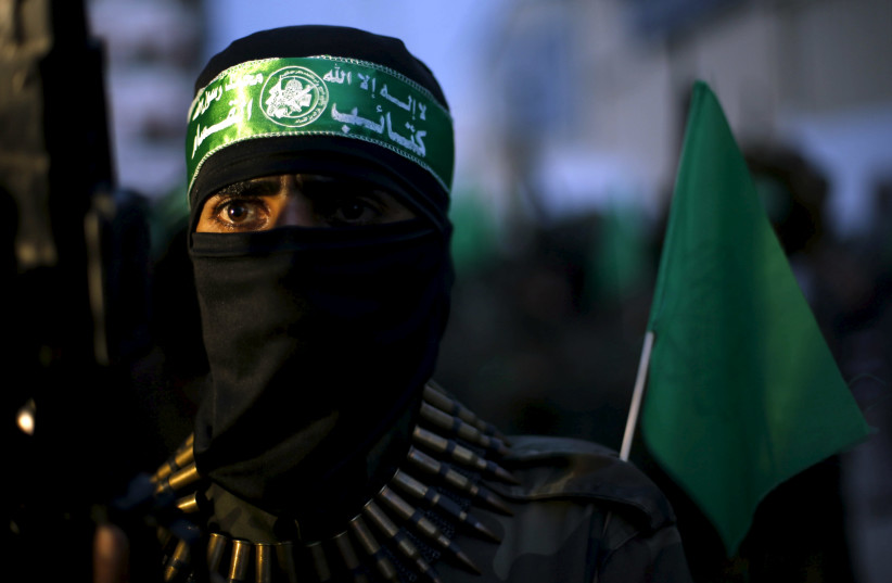 A Palestinian Hamas militant takes part in a Gaza rally marking the twelfth anniversary of the death of late Hamas leader Sheikh Ahmed Yassin. (photo credit: SUHAIB SALEM / REUTERS)