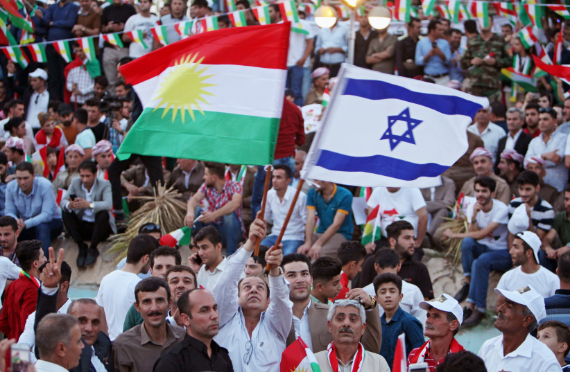 A Kurdish man holds an Israeli and Kurdish flag during a rally to show their support for the upcoming September 25th independence referendum in Erbil, Iraq September 16, 2017. (photo credit: REUTERS/AZAD LASHKARIG)
