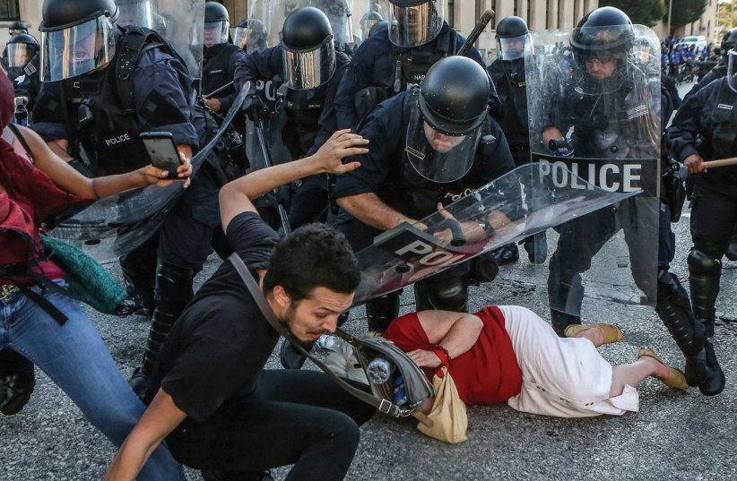 PROTESTERS FALL AS they are pushed back by St. Louis riot police during a protest on Friday following a not-guilty verdict in the murder trial of former police officer Jason Stockley (photo credit: REUTERS)