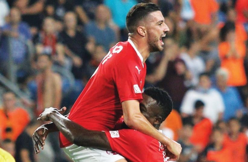 Hapoel Beersheba midfielder Niv Zrihen (top) jumps on teammate John Ogu after providing the cross that Bnei Yehuda's Paz Ben-Ari turned into his own net to give the visiting Southerners a 1-0 win in Petah Tikva (photo credit: ADI AVISHAI)