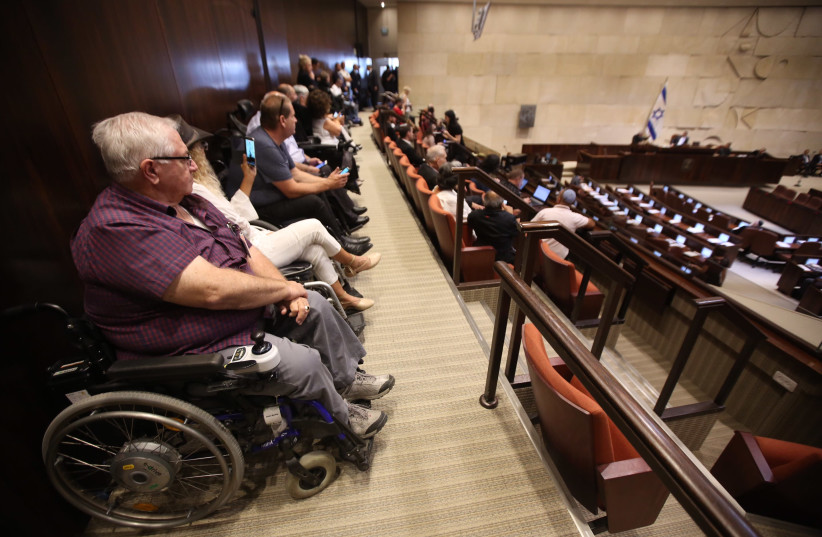 Disabled activists sit in at the Knesset plenum discussing goverment allowances for the disabled, September 18, 2017. (photo credit: MARC ISRAEL SELLEM/THE JERUSALEM POST)