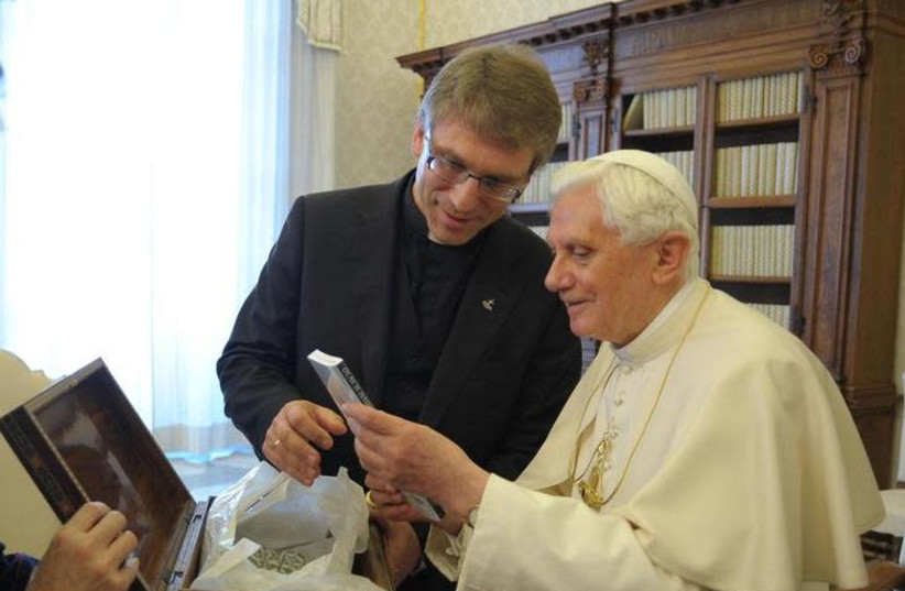 Pope Benedict XVI receives a book by Rev. Dr Olav Fykse Tveit, general-secretary of the World Council of Churches (WCC) (photo credit: OSSERVATORE ROMANO / REUTERS)