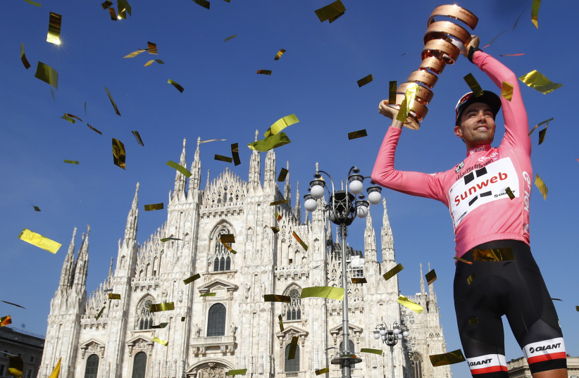 The winner of the 100th Giro d'Italia, Tour of Italy cycling race, Netherlands' Tom Dumoulin holds the trophy on the podium near Milan's cathedral after the last stage on May 28, 2017. (photo credit: AFP PHOTO)