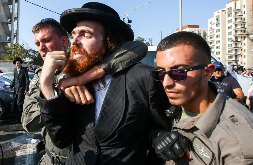 Police detain an ultra-Orthodox protestor at a violent anti-conscription protest in Jerusalem, September 17, 2017. (photo credit: MARC ISRAEL SELLEM)