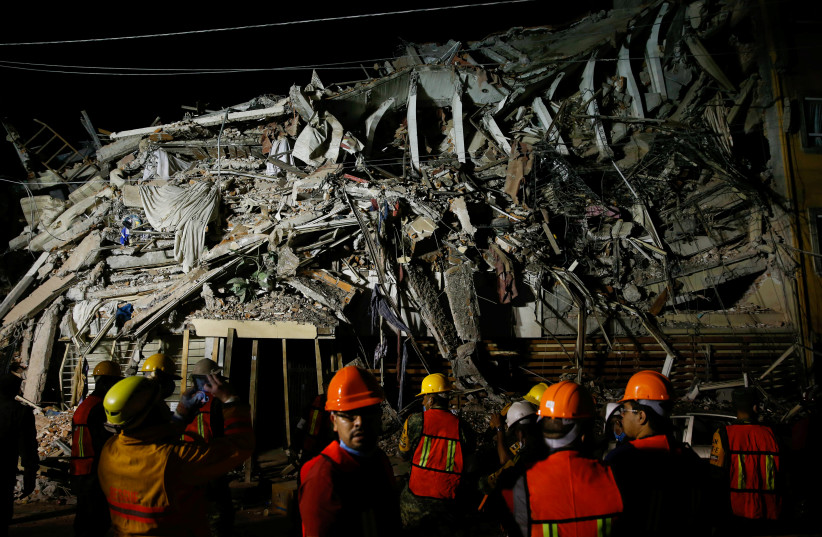 Rescuers work at a the site of a collapsed building after an earthquake in Mexico City (photo credit: REUTERS/HENRY ROMERO)