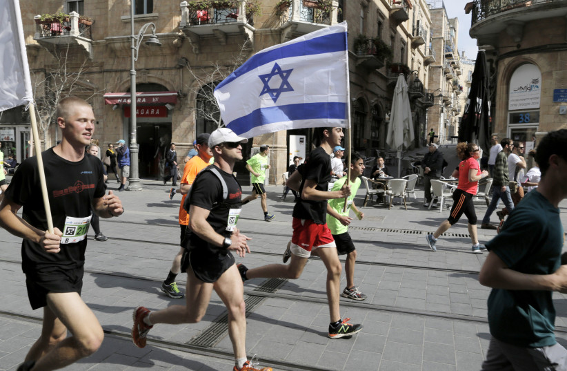 An athlete runs with an Israeli flag during the fifth international Jerusalem Marathon, March 13, 2015. (photo credit: REUTERS)