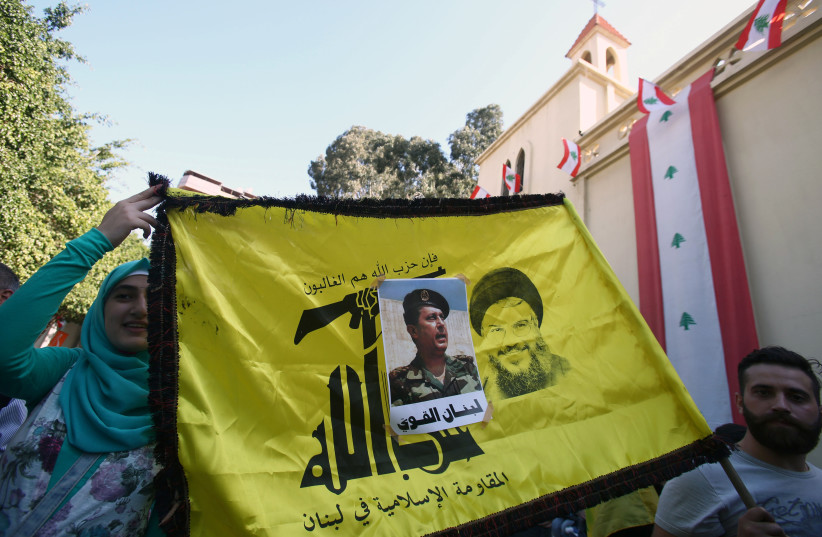 People carry a Hezbollah flag with a picture of newly appointed Lebanese President Michel Aoun stuck on it, in the Haret Hreik area, southern suburbs of Beirut, Lebanon October 31, 2016. (photo credit: REUTERS)