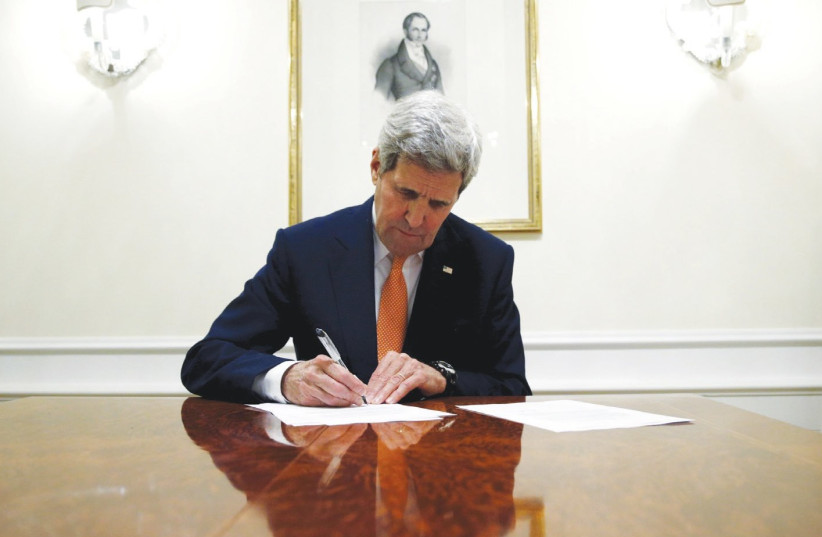 THEN-SECRETARY of state John Kerry signs the Iran deal in 2016. (photo credit: REUTERS)
