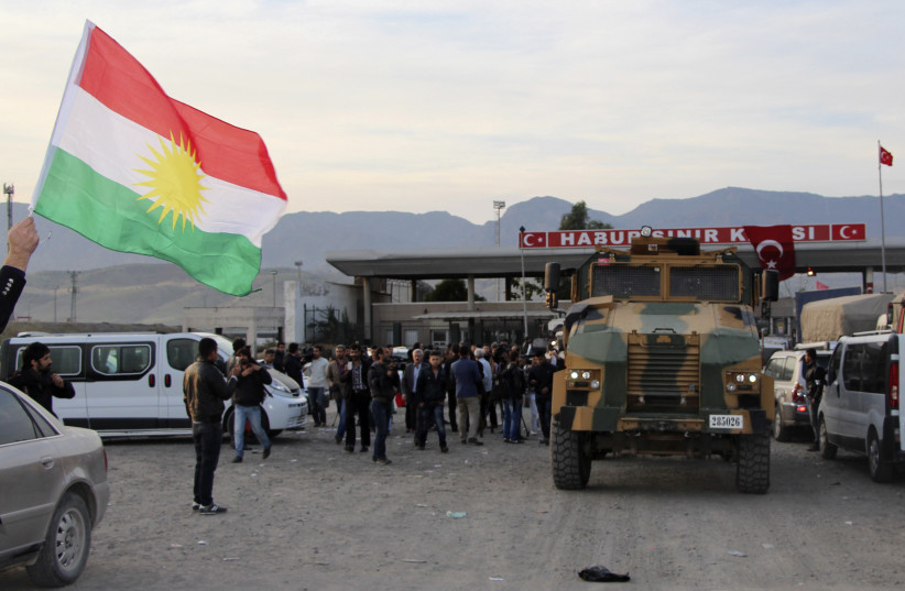 A man waves a Kurdistan flag as a Turkish military truck escorts a convoy of peshmerga vehicles at Habur border gate, which separates Turkey from Iraq, near the town of Silopi in southeastern Turkey. (photo credit: REUTERS)