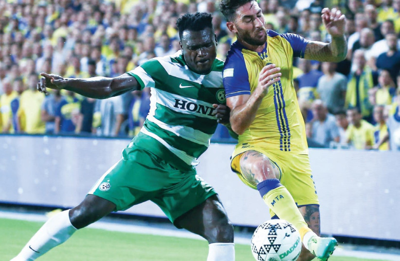 Maccabi Haifa defender Ernest Mabouka (left) and Maccabi Tel Aviv forward Eliran Atar battle for the ball during last night's 0-0 draw in Netanya.  (photo credit: DANNY MARON)