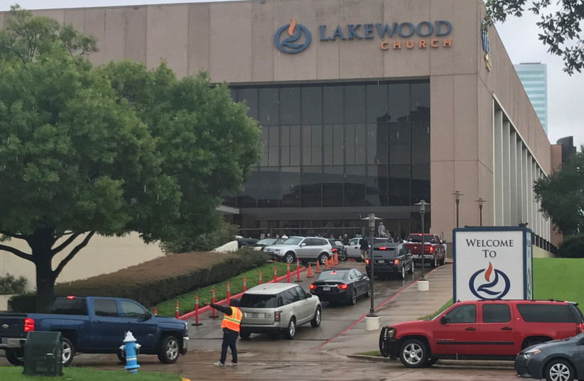 Vehicles queue to deliver supplies for Hurricane Harvey evacuees at the nondenominational Lakewood Church, founded by pastor Joel Osteen, in Houston, Texas, U.S. August 29, 2017 (photo credit: REUTERS/ERNEST SCHEYDER)