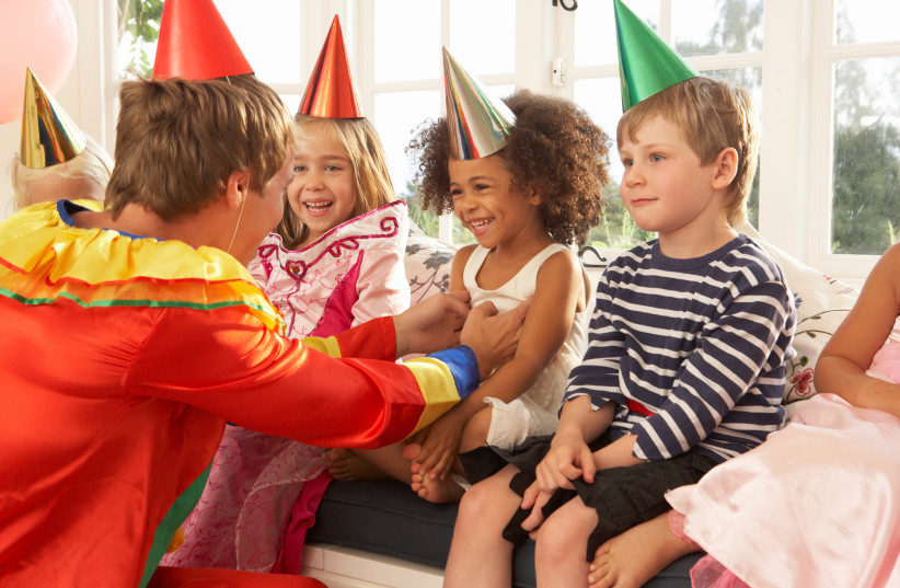 clown entertaining children at a party (photo credit: INGIMAGE)