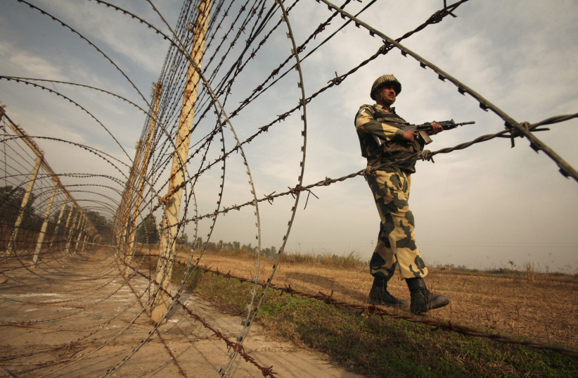 An Indian Border Security Forces soldier patrols near the fenced border with Pakistan (photo credit: MUKESH GUPTA / REUTERS)