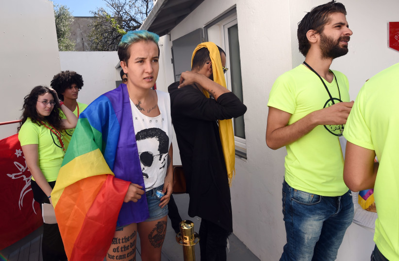 """Former Tunisian Femen activist Amina Sboui (C) and members of Tunisian """"Shams"""" association for the decriminalisation of homosexuality, wait before a press conference to support a 22-year-old man accused of engaging in homosexual acts and sentenced to a year in prison following an anal examination on (photo credit: FETHI BELAID/AFP)"""