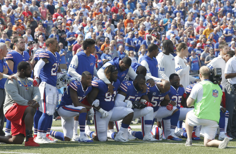 Buffalo Bills players kneel in protest during the anthem before a game against the Denver Broncos (photo credit: TIMOTHY T. LUDWIG-USA TODAY SPORTS / REUTERS)