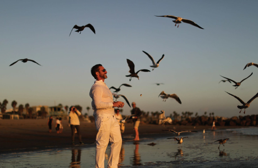 A MAN throws bread crumbs into the Pacific Ocean during the Tashlich prayer, a Rosh Hashana ritual to symbolically cast away sins, last week. (photo credit: REUTERS)