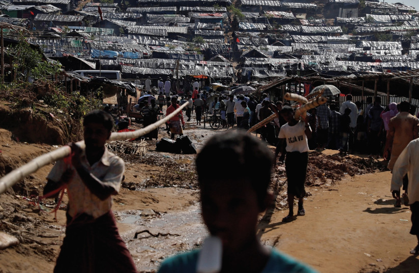 ROHINGYA REFUGEES walk through a camp in Cox's Bazar, Bangladesh, yesterday (photo credit: REUTERS)