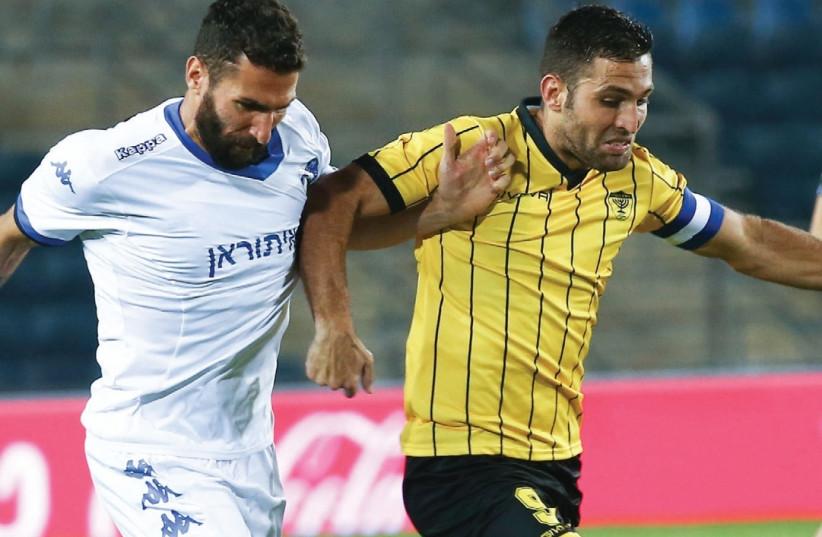 Beitar Jerusalem striker Itay Shechter and Ironi Kiryat Shmona defender Carlos Cuellar battle for the ball during last night's 1-1 draw at Teddy Stadium (photo credit: DANNY MAROM)