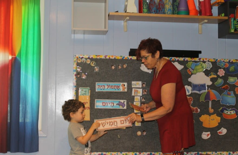 Tamar Pinto, who founded and runs the Gan Gurim preschool, teaching a student the Hebrew days of the week. (photo credit: BEN SALES)