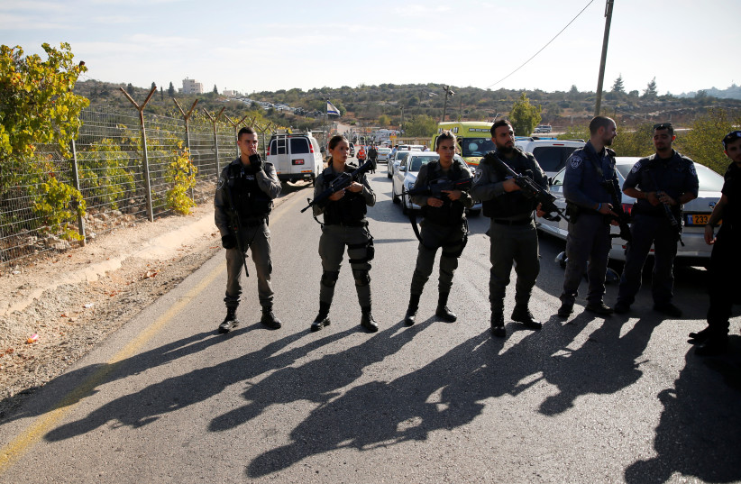 Border Police officers stand guard at the scene of the terror attack in Har Adar (photo credit: AMMAR AWAD / REUTERS)