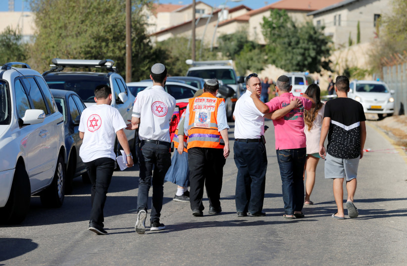 Medics and people at the scene where a Palestinian gunman killed three Israelis guards and wounded a fourth in a shooting attack  (photo credit: AMMAR AWAD / REUTERS)