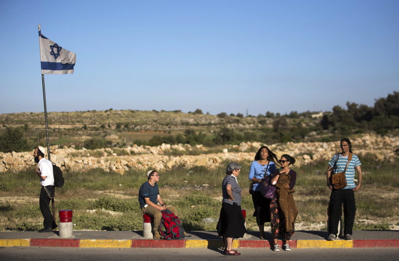 Israeli pedestrians stand on a roadside near the West Bank Jewish settlement of Efrat (photo credit: AMIR COHEN - REUTERS)
