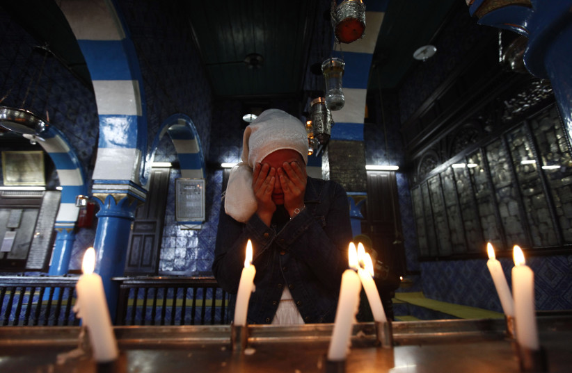 A Jewish woman lights candles during a pilgrimage to the El Ghriba synagogue in Djerba, Tunisia (photo credit: ANIS MILI / REUTERS)