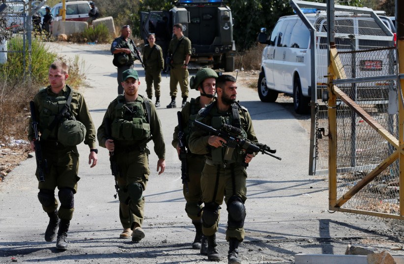 Israeli soldiers guard near the scene where a Palestinian gunman killed three Israelis and wounded a fourth in an attack on Har Adar before himself being shot dead, September 26, 2017. (photo credit: REUTERS)