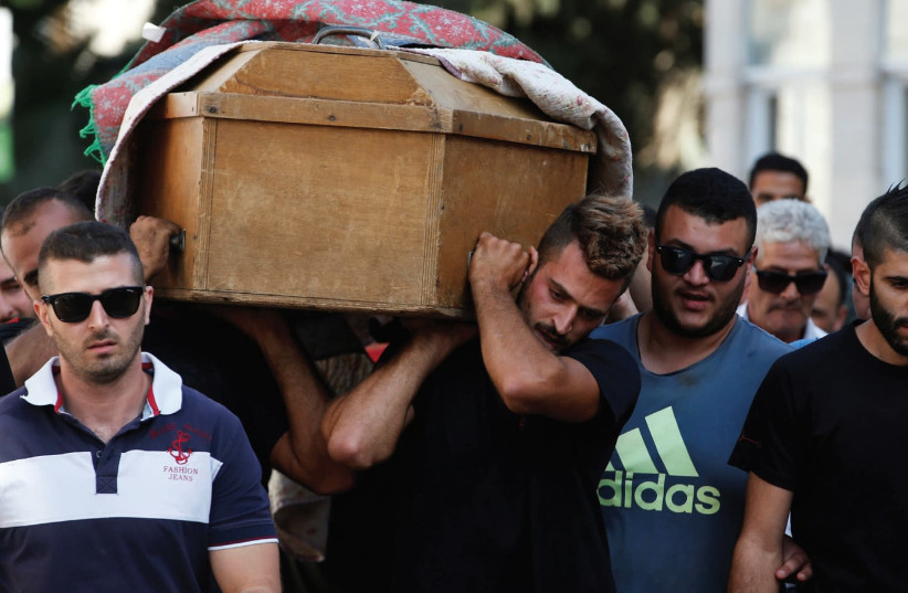 Relatives and friends carry the coffin of Youssef Othman, one of three guards killed in yesterday's terrorist attack, during his funeral in Abu Ghosh. (photo credit: RONEN ZVULUN / REUTERS)