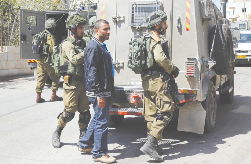 Soldiers arrest the brother of Har Adar terrorist Nimr Mahmoud Ahmad al-Jamal near Ramallah Tuesday. (photo credit: AMMAR AWAD / REUTERS)