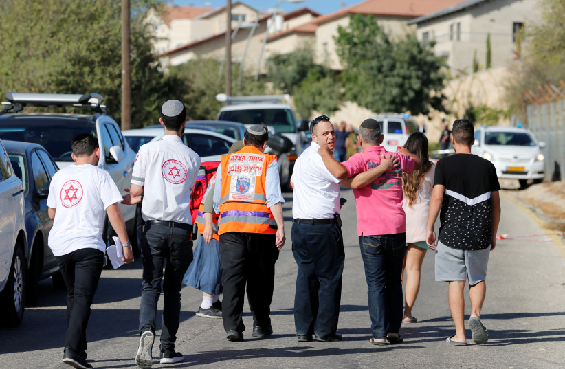 Medics and people walk at the scene where a Palestinian gunman killed three Israelis guards and wounded a fourth in an attack in Har Adar before himself being shot dead, September 26, 2017. (photo credit: REUTERS)