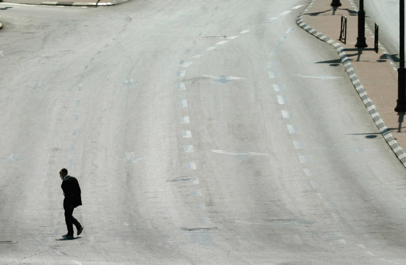 A MAN walks on an empty street in Jerusalem during Yom Kippur in this file photo from 2004. (photo credit: REINHARD KRAUSE/REUTERS)