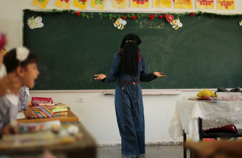 A veiled Palestinian teacher gestures as children attend a lesson at a United Nations Relief and Work Agency (UNRWA)-run school in Gaza (photo credit: REUTERS)