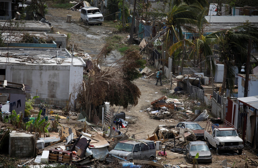 A man carrying a water container walks next to damaged houses after the area was hit by Hurricane Maria in Canovanas, Puerto Rico. (photo credit: CARLOS GARCIA RAWLINS/ REUTERS)