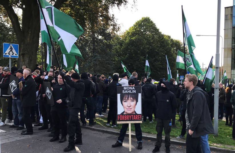"""Members of the Nordic Resistance Movement gather before a demonstration in Gothenburg, Sweden September 30, 2017. Placard reads """"Mona Sahlin is a criminal!"""" (photo credit: JOHAN AHLANDER/REUTERS)"""
