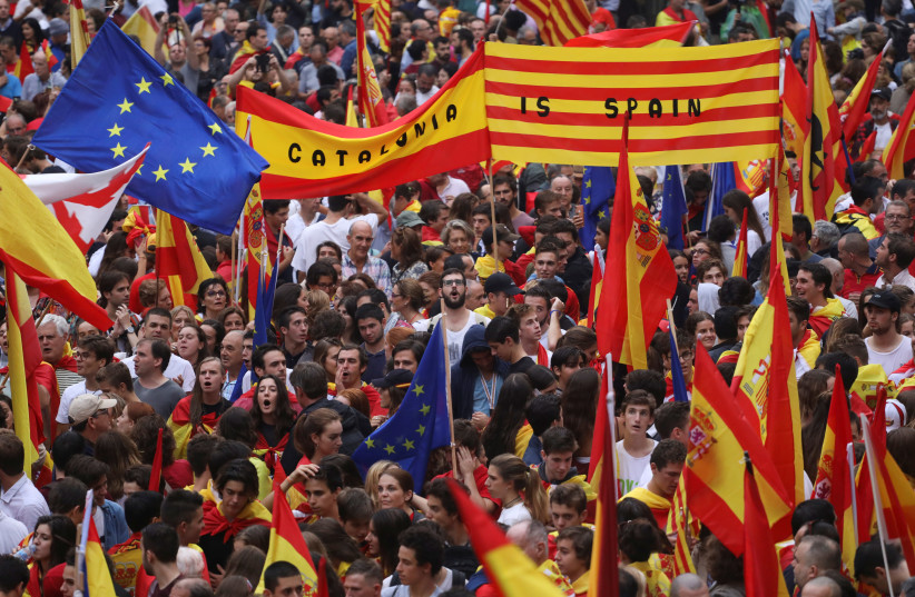 People wave Spanish, Catalan (known as Senyera) and European Union flags during a demonstration in favor of a unified Spain a day before the banned October 1 independence referendum, in Barcelona, Spain, September 30, 2017. (photo credit: REUTERS/SUSANA VERA)