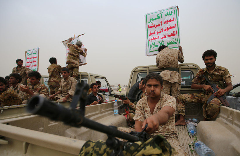 """Houthi fighters ride on the back of trucks as they take part in a parade in the Red Sea port city of Hodeidah, Yemen August 24, 2017. The placards read: """"Allah is the greatest. Death to America, death to Israel, a curse on the Jews, victory to Islam."""" (photo credit: REUTERS)"""
