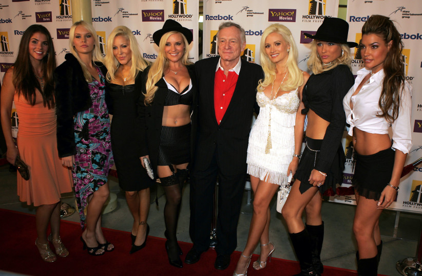 Playboy founder Hugh Hefner and his playmates pose (photo credit: STRINGER/ REUTERS)