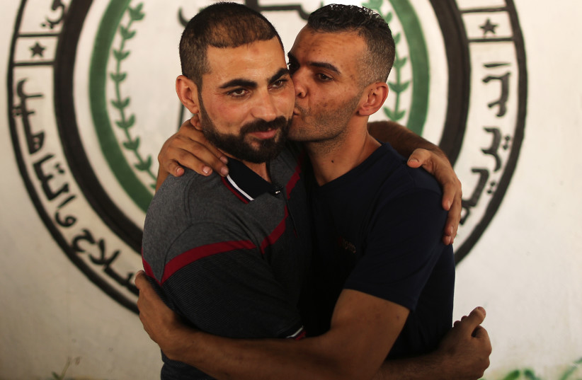 Shadi Abu Obeid (L), a member of the Palestinian Fatah movement, is greeted by a relative in Gaza City after his release from a Hamas prison on October 1, 2017. (photo credit: MAHMUD HAMS / AFP)